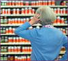 Photo: Woman standing before a wall of dietary supplements
