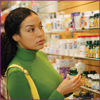 Photo: Woman in green examining dietary supplements at a store