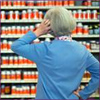 Photo: Woman standing in front of a display of dietary supplements