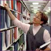 Photo: Woman pulling research studies from a shelf