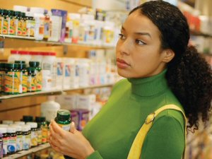 Woman looking at shelves of dietary supplement bottles