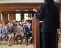 Woman at podium speaking to audience