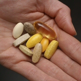 Hand holding supplement pills