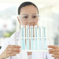 A lab technician looking at a set of vials filled with blue liquid
