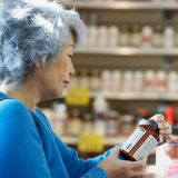 Woman inspecting a supplement bottle
