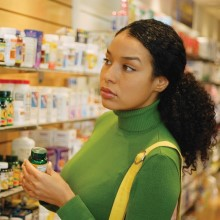 woman looking at supplements on a store shelf